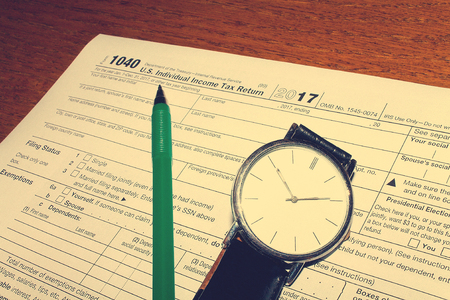 Tax day. The tax form 1040, green pen and hand watch is on a wooden table.