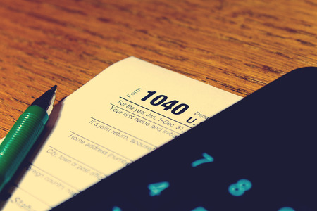 Tax day. The tax form 1040, green pen and black smartphone with calculator is on a wooden table.