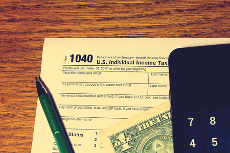 Tax day. The tax form 1040, green pen, black smartphone with calculator and dollar is on a wooden table.