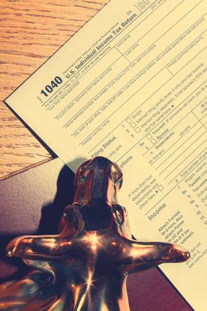 Tax day. The tax form 1040 and bull is on a wooden table. Banco de Imagens