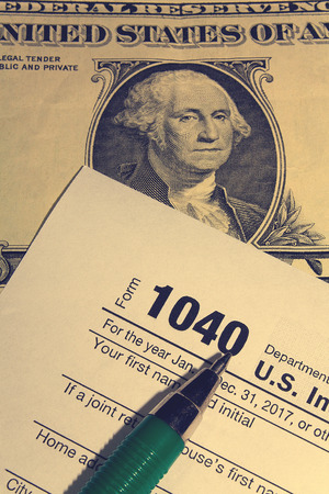 Tax day. The tax form 1040, green pen and dollar is on a wooden table.