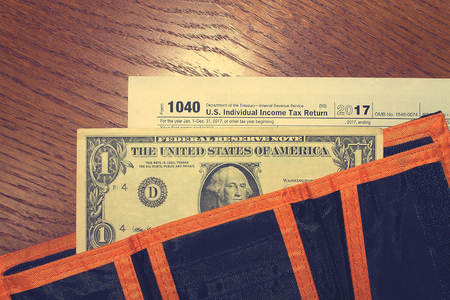 Tax day. The tax form 1040, dollar and orange black wallet is on a wooden table.