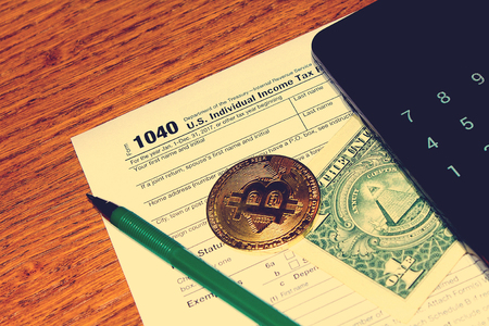Tax day. The tax form 1040, green pen, black smartphone with calculator, dollar and bitcoin is on a wooden table. Stock Photo