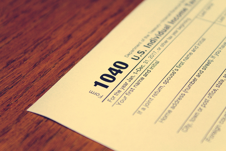 Tax day. The tax form 1040 is on a wooden table.