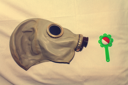 A toy in a gas mask as a concept for protecting children from the use of gas weapons, environmental pollution and the International Day of Remembrance for the Victims of the Chernobyl Catastrophe. Stock Photo