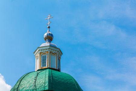 Green dome of a Christian temple with a silver cross against the blue sky with white clouds. Image contains copy space.