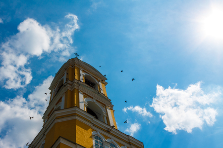 Tower of the Christian temple with bells and a cross into which flies black birds against the blue sky with white clouds.