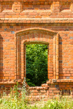 Window of the old destroyed building of red brick through which you can see green plants and grass.