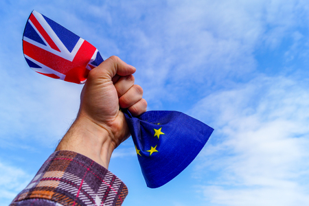 A male hand holds in his fist the flags of England and the European Union against a blue sky and symbolizes Brexit or No Brexit. Image contains copy space. Stock Photo