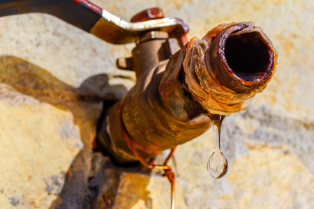 Close up image of a drop of water dripping from a rusty tap. Image can be used to illustrate water saving.