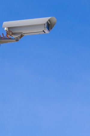 Security camera against the blue sky are monitoring. The image has a copy space.