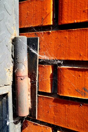 Old rusty door hinge with a spider web on a red brick wall. Old architecture.