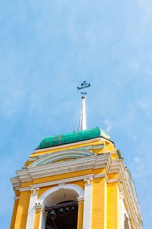 Yellow Orthodox Christian church with a green dome against a blue sky with white clouds.
