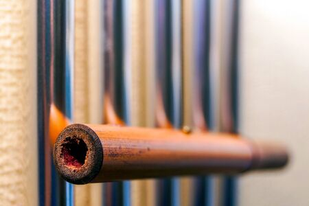 Metal tubular bells with a bamboo tube hang on the wall and create the music of the wind. Musical instrument.
