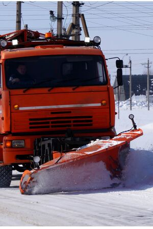 A large truck clears snow from the road. Seasons.