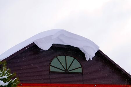 A lot of snow lies on a residential building and large snowdrifts around. Seasons.