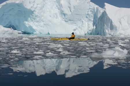 icebergs: One men in a kayak among icebergs in Antarctica