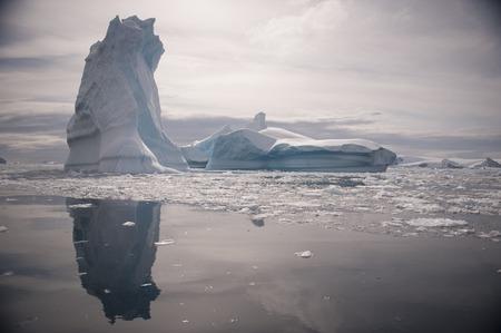 ocean water: Full calm and reflection of icebergs in deep clear water. Travel by the ship among ices. Snow and ices of the Antarctic islands.