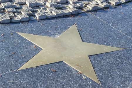 walk of fame: Bronze star in marble pavement