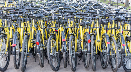 campus tour: Plenty of yellow bikes parked near a bicycle rental station in a park in Bucharest Romania Stock Photo
