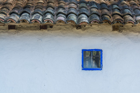 thatched: Authentic Romanian village house  built with natural bio materials and ancient techniques in traditional architecture. Closeup on blue painted window frame and traditional tiles