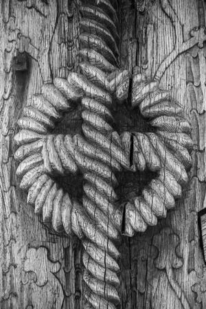 sculpted: Closeup detail of a ancient Romanian traditional sculpted gate by an unknown craftsmen 100 years ago. Wooden texture background