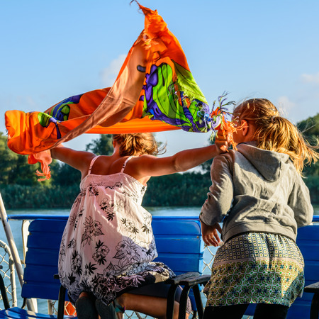 sightseeng: Two girls on the viewing platform.  One of the girls holding a shawl. Happy cute girls on sightseeng tour. Stock Photo