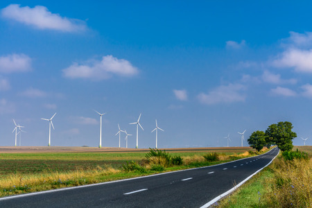 energy picture: Landscape of wind turbines and an asphalt road stretching into the distance. Bright picture of  wind turbines generating energy along the road. Stock Photo