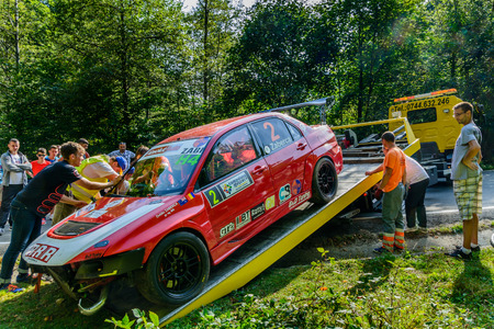 racer flag: CAMPLUNG, ROMANIA - September 27: Rally car after accident in Campulung Romania on September 27, 2015. Tow truck plunges a sport car after an accident