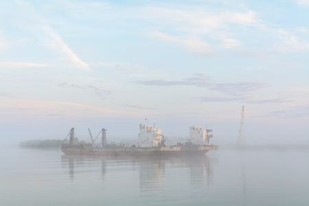 danubian: Lake boat engulfed with fog. Horizontal view of a commercial boat leaving the harbor, early in the morning.
