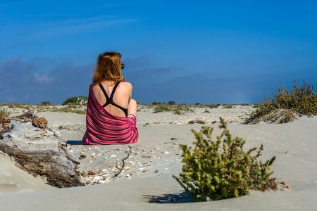 traje de bano: La mujer joven en traje casual sentado en la playa. Vista horizontal de una mujer en un vestido de color rosa cerca de una flor frente a la l�nea del horizonte, en un d�a soleado en verano.