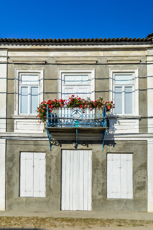 well maintained: Simple balcony of a one-story house, with well maintained  old house, with white windows and door, and a balcony with red flowers. Stock Photo