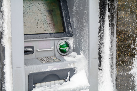 automatic teller machine bank: Atm machine covered with snow. Functional bank atm machine covered with ice and snow.