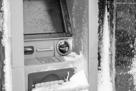 pincode: Atm machine covered with snow. Black and white picture of functional bank atm machine covered with ice and snow.