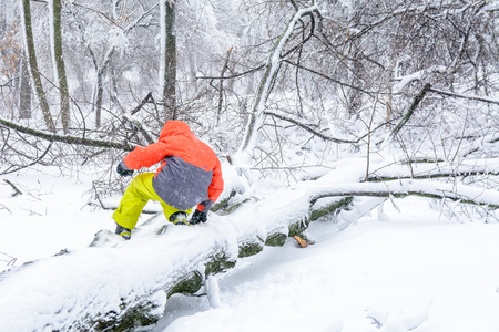 snow climbing: Child climbing over fallen down trunk. Sport, leisure, recreation and healthy active lifestyle concept - child climbing on a fallen trunk in snow. Stock Photo
