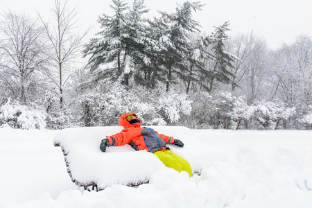 winter fun: Little boy laying on bench with snow. Horizontal view with child in winter clothes spreading hands and feet over snow bench - winter fun. Stock Photo
