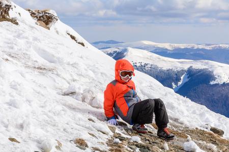ropa de invierno: Boy playing on mountain in wintertime. Cute little kid boy in colorful winter clothes and glasses playing on mountain covered with snow. Foto de archivo