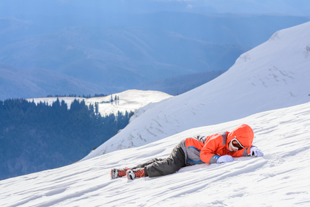 Boy fell down over fresh snow. Happy boy laying on snow. Cute little kid boy in colorful winter clothes laying down on snow, hand gloves, winter fashion.