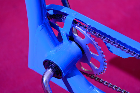 Bike gears with chain (selective focus). Colorful close up of a bicycle gear with details, chain and gearshift mechanism.