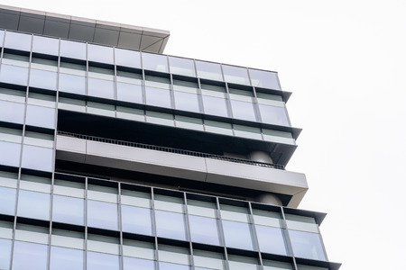 architectural exterior: Extreme close up building windows. Low angle view of modern commercial office building with vertical windows, architectural exterior against white sky.