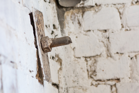 screw head: Old screw head in brick. Realistic image with old rusty screw head, bolt, wheel screw isolated on brick wall background.