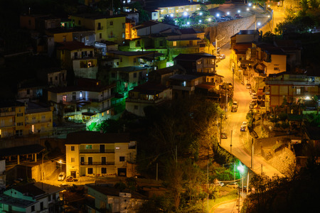 lighted: Lighted street at night in Italy. Panoramic view with lighted street at night, cars and villas.
