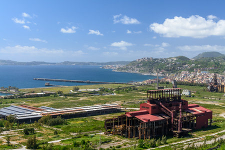 Panoramic view with industrial area in front. Calm sky and sea, mounts in background, houses, industrial building in front. Editorial