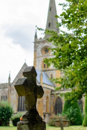 memorial cross: cruz de hormigón con la iglesia detrás. Vista vertical con la cruz de hormigón junto a las ramas verdes, con la iglesia católica atrás.