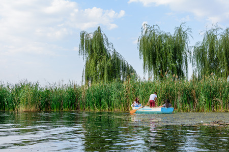 Young people in boat over lake. Boy and two girls in boat over calm lake with willows and reed behind. Stock Photo