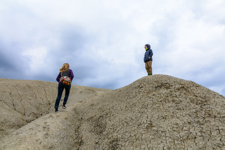 regnant: Mother and son visiting muddy volcano. Family climbing dry arid hill, visiting muddy volcano.