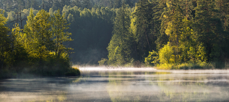 A beautiful European landscape taken in the region of a thousand lakes, in Belarus. We can see lake and forests with morning`s.The autumn landscape, shot at dawn. The lake in the fog and the first rays of the sun.Panorama of an autumn belorussian forest l