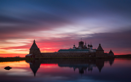 Fantastically beautiful sunset on the Holy Lake with a view of the Solovetsky Spaso-Preobrazhensky Transfiguration Monastery. White Sea, Russia, Arkhangelsk region, Solovki island