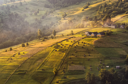 Scenic view early summer morning in a small Carpathian village. The first rays of the sun lit slopes The carpathian rolling landscape on a sunset in summer colors. West Ukraine Reklamní fotografie