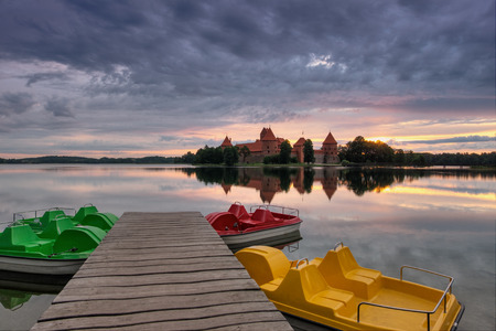 Fantastically fiery summer sunrise over Trakai Island Castle in Lithuania, with a beautiful reflection and the sun`s rays over the castle and colorful water bicycles. Trakai Island Castle in Lithuania, with a beautiful reflection, sun`s rays over the cast